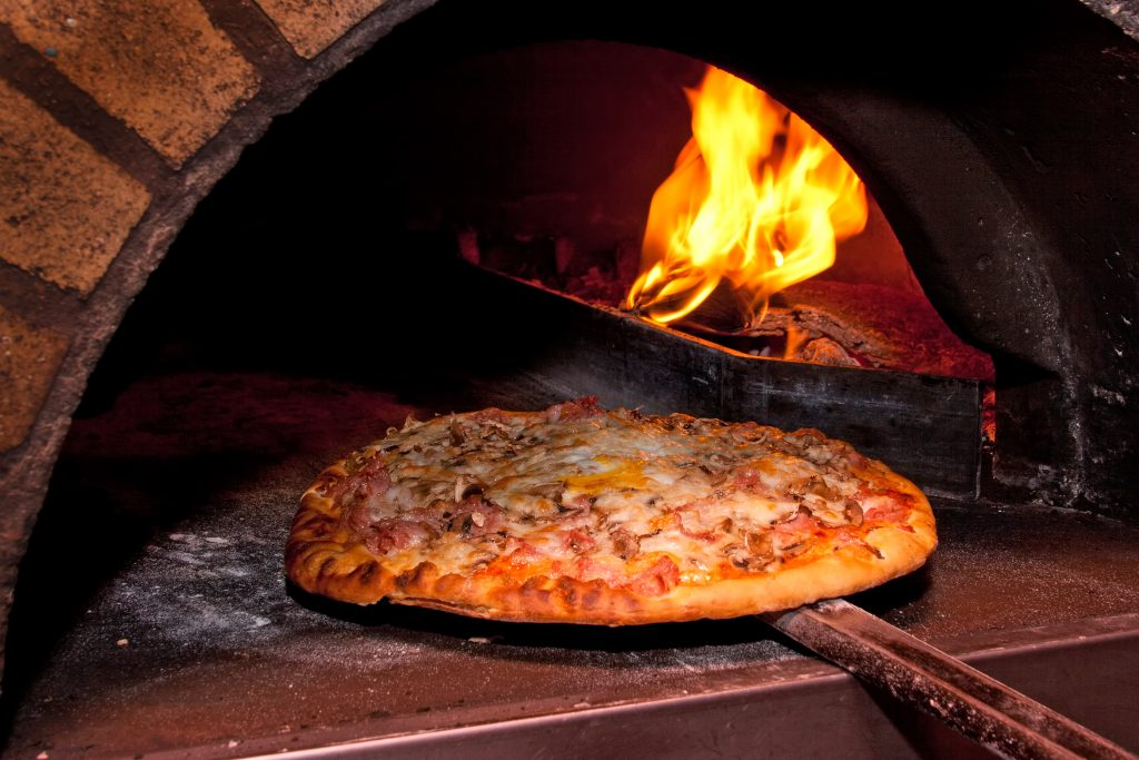 pizza being placed into a brick oven