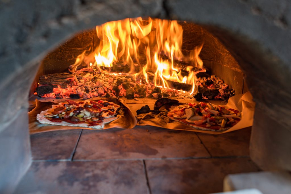 pizzas in a fire burning oven